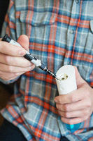 A man in a checkered shirt repairs an irrigator for cleaning teeth. Caries protection. Oral hygiene.