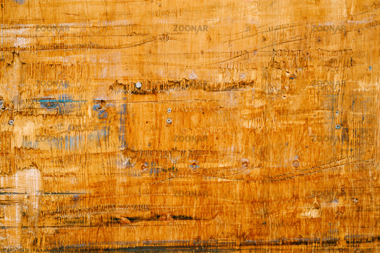 An old wooden board with nails and rough patches.