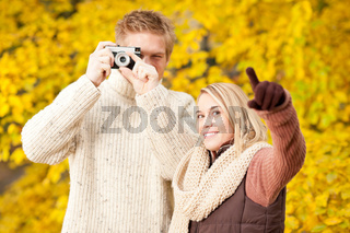 Autumn couple take photo camera in park