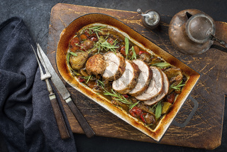 Traditional braised veal roll roast sliced with vegetable and herbs offered as top view in a rustic skillet