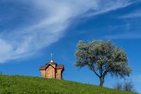 Small old wooden chapel on summer green grassy hill top, lonely willow tree and blue sky with cloud.