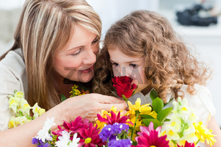 Little girl smelling flowers while her grandmother is smilling