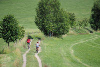 Mother with her son ride a bike in the summer countryside
