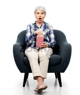 senior woman eating popcorn sitting in armchair