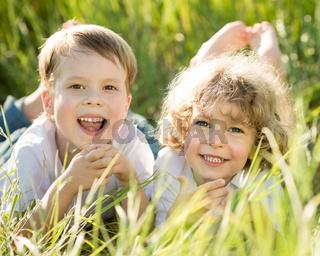Happy children lying on grass