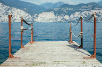 Summer holiday: Wooden dock pier over blue lake water, text space.