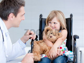 Smiling little girl sitting on the wheelchair lokking at the doctor