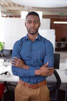 Portrait of african american businessman standing in office with arms crossed looking to camera