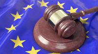 Judge's gavel lies on top of the EU flag