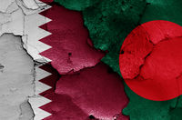 flags of Qatar and Bangladesh painted on cracked wall