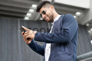 Handsome man using mobile phone app texting outside of office in urban city with skyscrapers buildings in the background. Young man holding smartphone for business work.