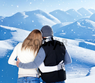 Happy couple hugging outdoor at winter mountains, rear view