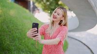 Cheerful female taking selfie in park