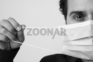 Black and white close-up portrait of a man wearing protective medical mask.