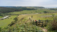 ALFRISTON, EAST SUSSEX, UK - SEPTEMBER 13 : Person taking a photo of the Cuckmere river valley from High and Over viewpoint near Alfriston, East Sussex on September 13, 2021. Unidentified woman