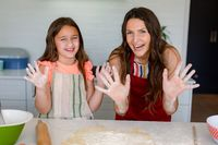 Happy caucasian mother and daughter baking together, showing hands dirty with dough