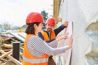 Architektin und Polier besprechen Gebäudesanierung