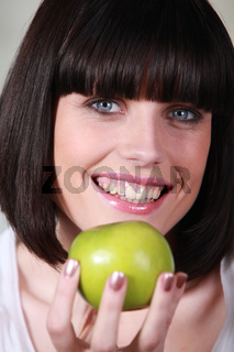 Woman with a big smile and a green apple