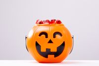 Composition of halloween bucket with trick or treat sweets on white background