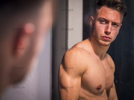 Shirtless muscular handsome young man in the bathroom