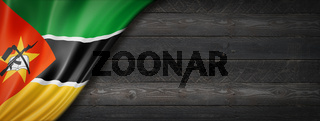 Mozambique flag on black wood wall banner