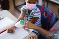 Mid section of female health worker measuring temperature of a girl at elementary school