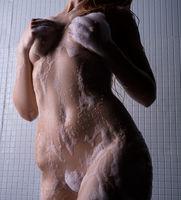 Nude woman body covererd by shower foam cropped shot