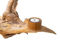 Burning tealight stands on a light tree root, isolated on white as a decoration