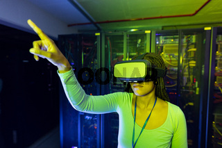 African american female computer technician wearing vr headset and working in server room