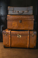 Pile of vintage warn travel suitcases or trunks on the floor