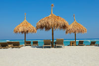 Thatched shades on a scenic tropical island beach