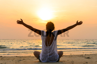 woman is sitting on beach at sunrise