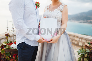 The bride and groom are embracing and holding a marriage certificate in their hands, close-up
