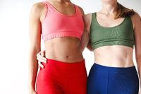 Two joyful happy women in sportive pink hoodie taking break after yoga classes