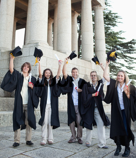 Five happy grad students raising their hats