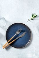 Blue ceramic plate, shot from the above with cutlery and an olive branch