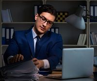Businessman working late at night in office for overtime bonus