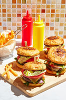 Appetizing homemade burgers on wooden cutting board with bright sunlight. Burger with veal cutlets, pamidorom, cheese, red onion, lettuce, rocket salad and french fries. Fast food concept