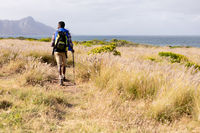 Fit african american man wearing backpack nordic walking on coast
