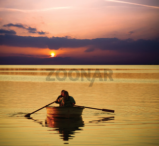 Couple relaxing on boat at sunset