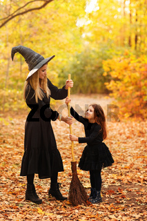 Mother and daughter sweeping path on Halloween day
