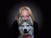 Portrait of a girl and a dog with blue eyes on a dark background