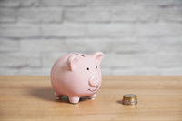 Piggy bank with stack of euro coins on table