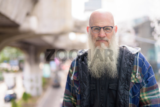 Mature bald bearded man wearing eyeglasses in the city streets outdoors