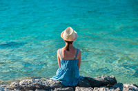 Little girl in a blue summer dress and a straw hat sitting on a rocky shore of the sea - a shot from behind her back