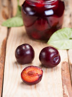 Plums on rough wooden table. In background glass jar with jam.