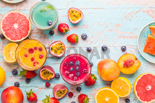 Variation of smoothies and refreshing drinks with fresh fruits for hot summer on blue background
