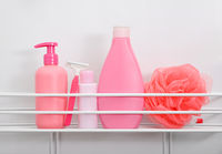 Pink bottles of hygiene toiletries in white bath