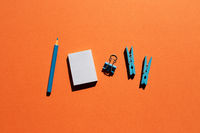 Blue memo notepad, clips, colored pencil on red background. Work and study place. flat lay, top view, copy space