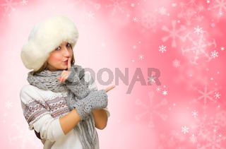 Young girl in fur hat on red snowy background